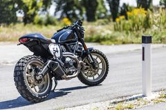 Custom made scrambler style cafe racer standing on road stock images