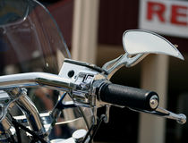 Custom motorcycle mirror. A close up view of a unique, custom mirror on the handlebar of a motorcycle Royalty Free Stock Photography