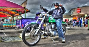 Custom painted 1980s Harley Davidson Softail. Custom painted green 1987 Harley Davidson Softail motorcycle and bikie at a car and bike show held in Melbourne stock image