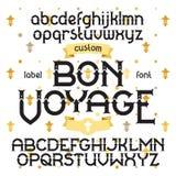 Custom retro typeface Bon Voyage. Vintage alphabet font set on the background of gold royal heraldic lilies Stock Image