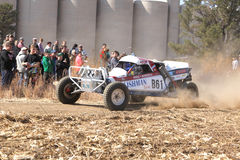 Custom single seater rally buggy kicking up trail of dust on san Stock Photos
