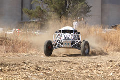 Custom single seater rally buggy kicking up trail of dust on san Royalty Free Stock Photography