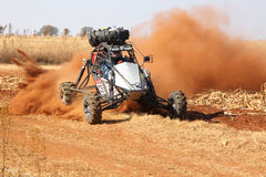 Custom single seater rally buggy kicking up trail of dust on san Stock Images