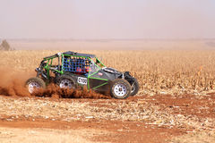Custom single seater rally buggy kicking up trail of dust on san Royalty Free Stock Image