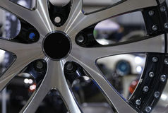 Custom Alloy Sport Wheel at Car Show. Automotive sport wheel with car visible between spokes Royalty Free Stock Photos