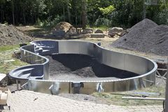 Custom swimming pool installation. A custom swimming pool in the stages of construction Royalty Free Stock Image