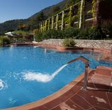 Custom swimming pool and vine covered resort. A oversized pool fixture pours water into a beautiful relaxing swimming pool at a luxury resort in the Alps of Royalty Free Stock Photo