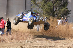 Custom twin seater rally buggy airborne over bump on sand track Stock Images