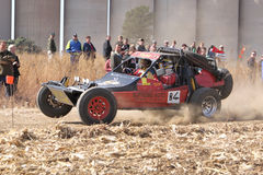Custom twin seater rally buggy kicking up trail of dust on sand Royalty Free Stock Images