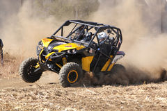 Custom twin seater rally buggy kicking up trail of dust on sand Royalty Free Stock Image