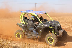 Custom twin seater rally buggy kicking up trail of dust on sand Stock Photography