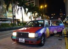 Customer alight from Hong Kong taxi. HONG KONG - NOVEMBER 22 : Customer alight from a red taxi in Hong Kong on November 22, 2014.Taxi is a popular public Royalty Free Stock Photos