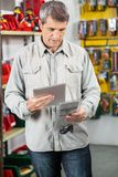 Customer Analyzing Product Through Digital Tablet. Mature male customer analyzing product through digital tablet in hardware store Stock Image