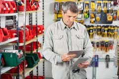 Customer Analyzing Product Through Digital Tablet. Mature male customer analyzing product through digital tablet in hardware store Royalty Free Stock Photos