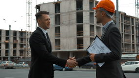 Customer and architecture shaking hands. Slow motion. Two Young successful business people shaking hands. Architect in orange helmet with text pad, Customer in stock video footage