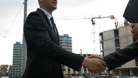 Customer and architecture shaking hands. Slow motion. Two Young successful business people shaking hands. Architector in helmet with text pad, Customer in suit stock footage