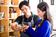 Customer in an Asian Pottery shop. Asian seller or souvenir dealer speaks with an Indonesian customer at a shop and shows her pottery Royalty Free Stock Photos