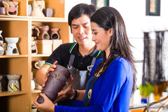 Customer in an Asian Pottery shop. Asian seller or souvenir dealer speaks with an Indonesian customer at a shop and shows her pottery Royalty Free Stock Images
