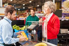 Free Customer At Supermarket Checkout Looks Over Cashier Royalty Free Stock Images - 158856249