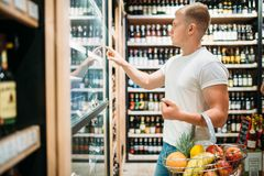 Customer with basket choosing beer in supermarket. Male customer with basket choosing beer in supermarket. Shopping in food store, alcohol section on background stock image
