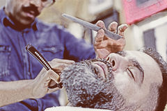 Customer on a beard shaving session Royalty Free Stock Images