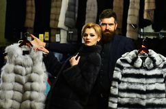 Customer with beard and woman buy furry coats. Customer with beard and women buy furry coats. Man and girl with serious faces hold furry coats on clothes rack royalty free stock image