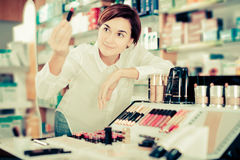 Customer browsing rows of cosmetic products Stock Images