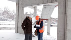 The customer, a business man, discusses the construction of his new shopping center with the architect and engineer stock video