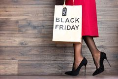 Customer buyer legs of woman female adult with shopping bag with sale label and black high heels walking to fashion shopping mall royalty free stock image
