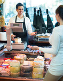 Customer buying cheese for dessert. Female customer buying cheese for dessert in delicatessen store Royalty Free Stock Image