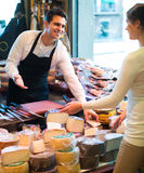 Customer buying cheese for dessert. Positive female customer buying cheese for dessert in delicatessen store Stock Photography