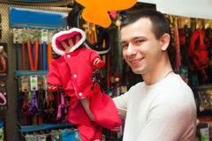 Customer buying clothes for pet. Portrait of ordinary male customer buying clothes for pet in shop Royalty Free Stock Photos