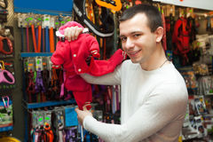 Customer buying clothes for pet. Portrait of ordinary male customer buying clothes for pet in zoo shop Stock Photography