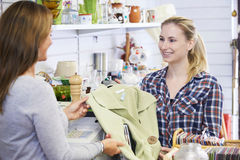 Customer Buying Clothing In Charity Shop Stock Photos