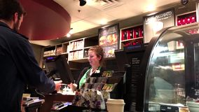 Customer buying coffee and paying by iphone mobile app stock footage