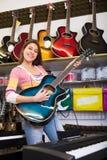 Customer buying new guitar Stock Image