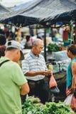 Customer buying vegetables at fresh market. A Chinese man buying some vegetables from a fresh market at Sri Aman town stock image