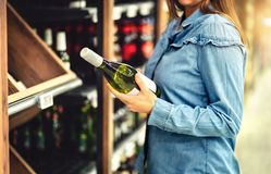 Customer buying white wine or sparkling drink. Alcohol aisle in store or supermarket. Woman holding bottle. royalty free stock photo
