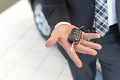 Customer in the car dealership holds the car key of the newly pu stock photo