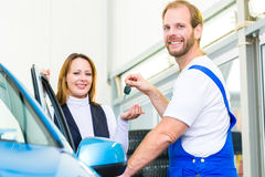 Customer and car mechanic in auto workshop Stock Images