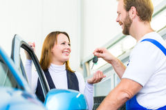 Customer and car mechanic in auto workshop Stock Photo