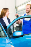 Customer and car mechanic in auto workshop Stock Photos