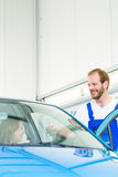 Customer and car mechanic in workshop Stock Photo