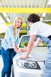 Customer and car painter in auto workshop Royalty Free Stock Image