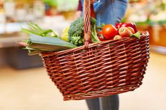 Customer carrying shopping basket with vegetables. Customer carrying full shopping basket with fresh vegetables in a supermarket Royalty Free Stock Image