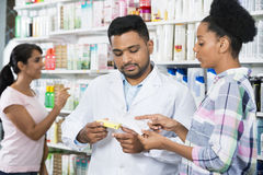 Customer And Chemist With Prescription In Pharmacy. Female customer and male chemist with prescription in pharmacy royalty free stock images