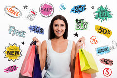 Customer choice. Cheerful young woman in dress carrying colorful shopping bags and looking at camera with colorful sketches upon her head Royalty Free Stock Image
