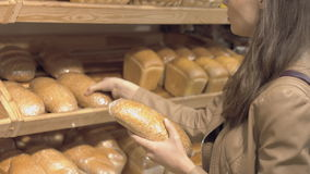 Customer chooses the bread in a supermarket. Customer chooses the bread in the supermarket stock video footage