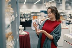 Customer choosing crystal glasses utensil dishes in the supermarket mall. Female customer choosing crystal glasses utensil dishes in the supermarket mall Stock Image