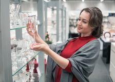 Customer choosing crystal glasses utensil dishes in the supermarket mall. Female customer choosing crystal glasses utensil dishes in the supermarket mall Stock Images